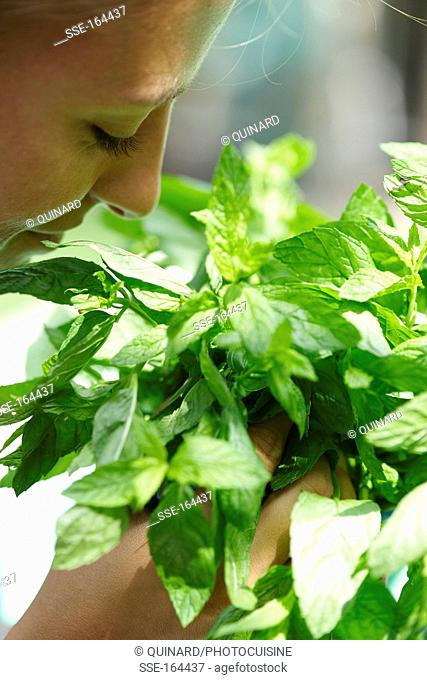 Woman smelling a bunch of fresh mint