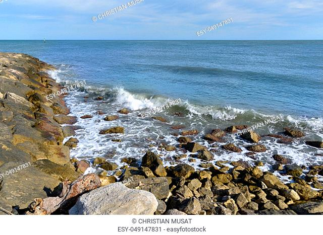 Rocky coast at Saintes-Maries-de-la-Mer, a commune in the Bouches-du-Rhône department by the Mediterranean Sea in the south of France