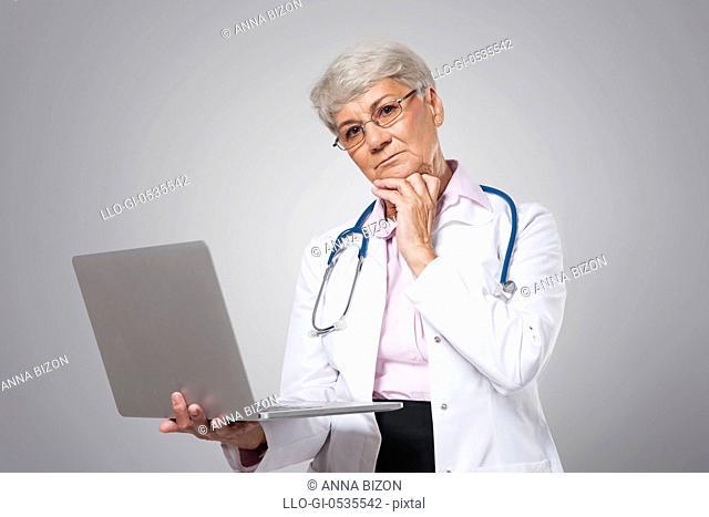 Worried female senior doctor with laptop. Debica, Poland