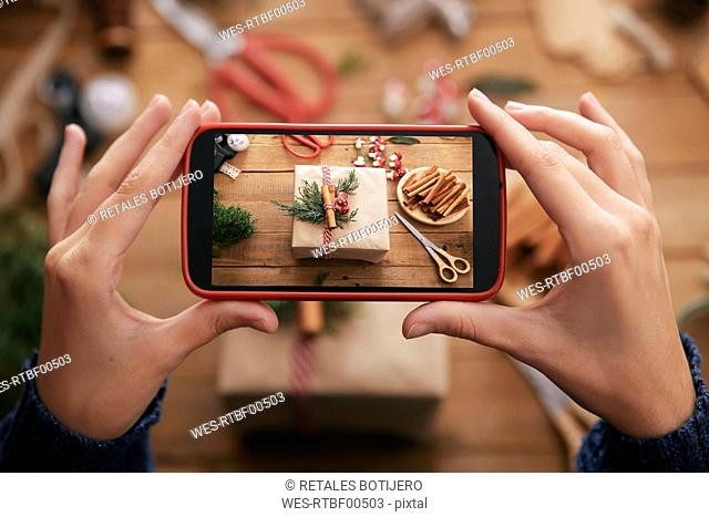 Woman photographing decorated Christmas gift with smartphone, close-up