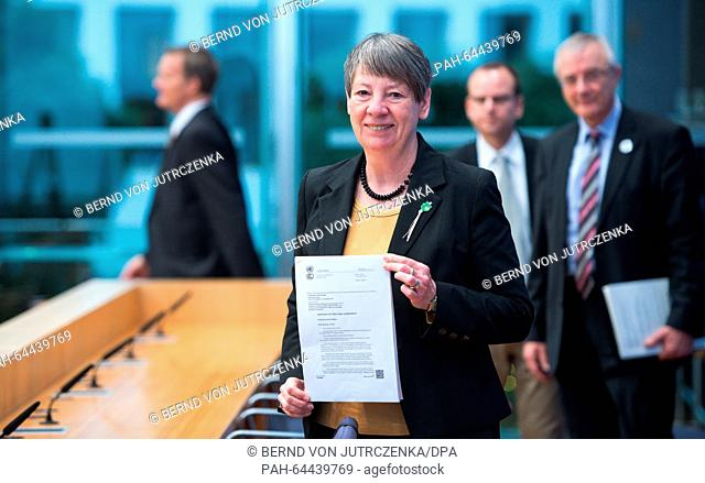 German Environmental Minister Barbara Hendricks speaks about the results of the UN Climate Change Conference inParis and holds up the signed climate agreement...