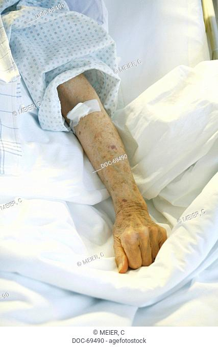 Plastered forearm of an elderly person, lying on a blanket