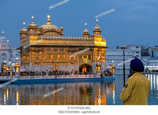 India, Punjab, Amritsar, Portrait of Sikh guard holding spear at Golden Temple
