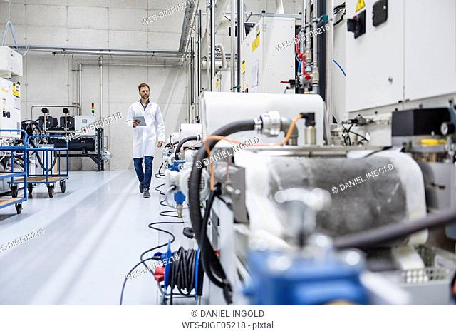 Employee checking manufacturing machines in high tech company, using digital tablet