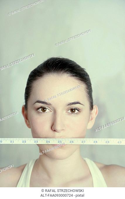 Woman holding measuring tape across mouth, close-up