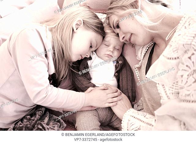 Mother with baby son and daughter resting on the sofa
