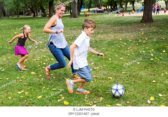 A mother playing soccer with her kids in a park during a family outing; Edmonton, Alberta, Canada