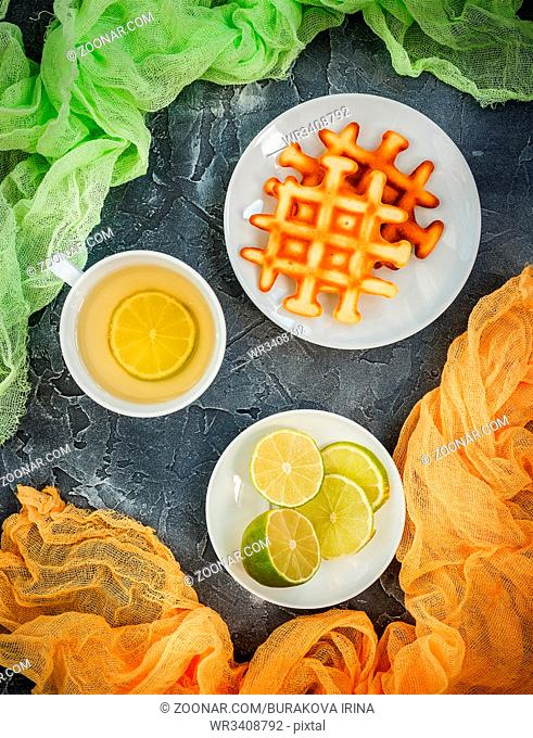 Belgian waffles on white plate, cup of green tea, sliced lime on grey background. Top view
