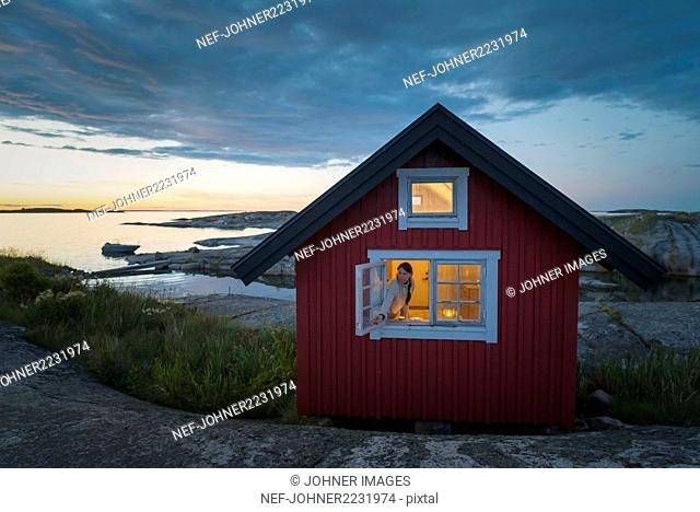 Woman in wooden house at sea