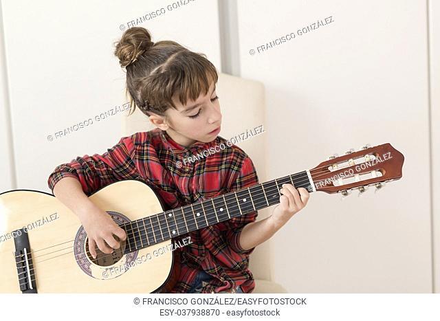 10 year old girl playing the Spanish guitar. Horizontal shot