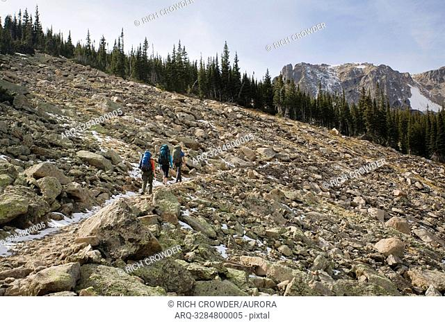 A man and two women hiking through a talus field on the Fern Lake Trail in Rocky Mountain National Park, Colorado