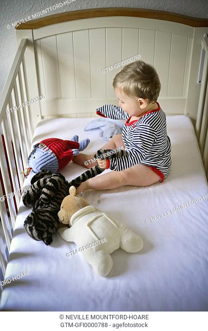 Baby sitting and playing with soft toys in cot
