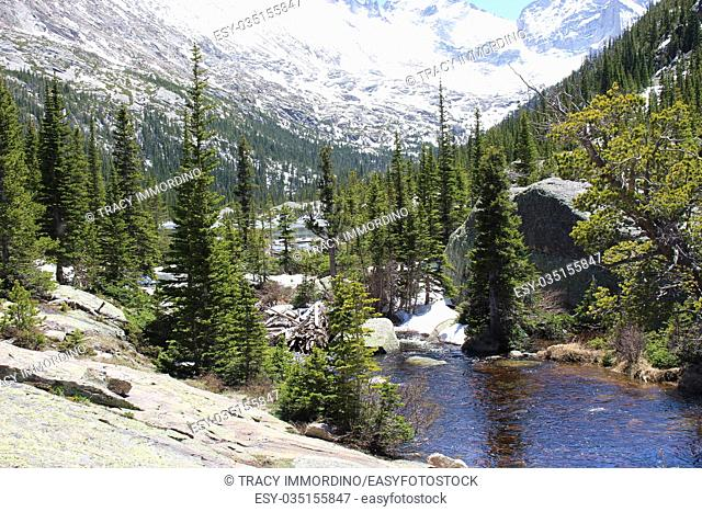 Glacier Creek flowing into Mills Lake in Rocky Mountain National Park, Colorado, USA, surrounded by snow and pine covered mountain peaks