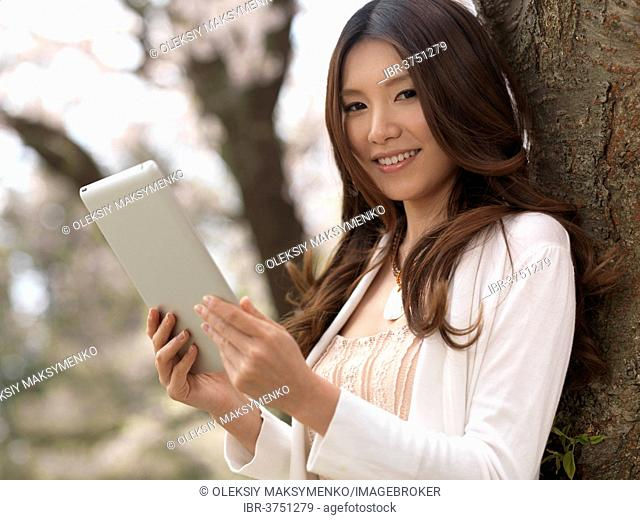 Young woman holding a tablet computer standing in a park, Toronto, Ontario Province, Canada