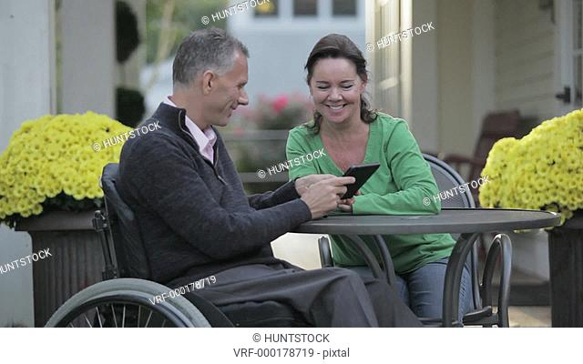 Man with spinal cord injury in a wheelchair looking at a tablet with his wife at a cafe