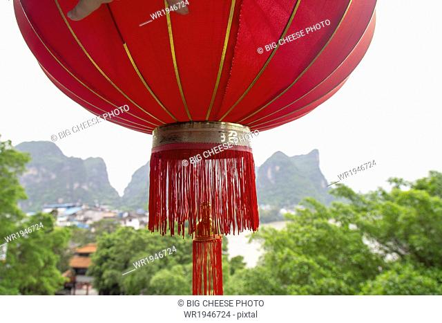Red lantern hanging in front of a view of the Karst mountains and Li River, Yangshuo, China