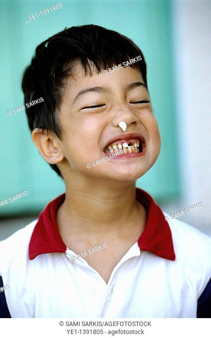 Six year old boy with a missing tooth making a silly face, France