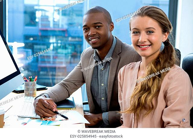 Portrait of graphic designer at desk with colleague