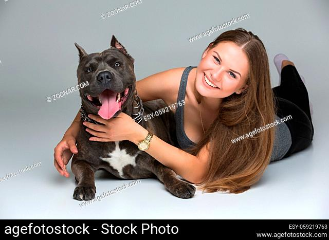 Beautiful sporty young woman lying on floor and hugging adult grey amstafford terrier dog. Studio shot over gray background. Copy space