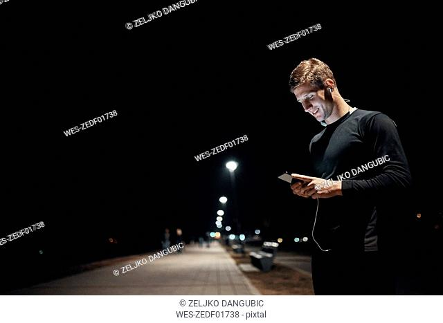 Sportive young man with smartphone and earphones outdoors at night