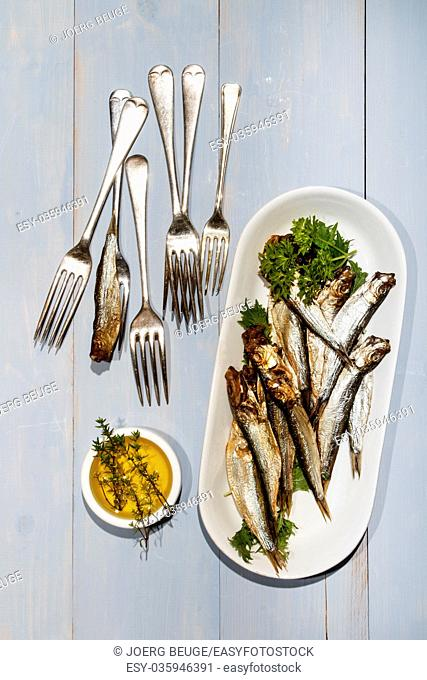 sprats and parsley on a plate, a small bowl with olive oil and thyme on an old table