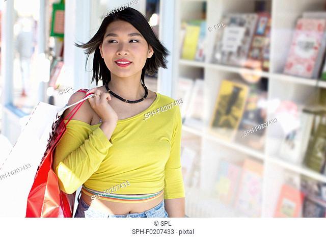 Woman walking past book shop window
