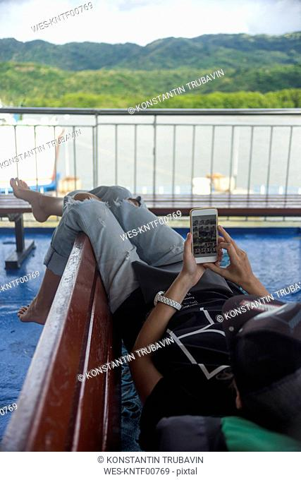 Indonesia, Lombok island, woman using cell phone on ship deck