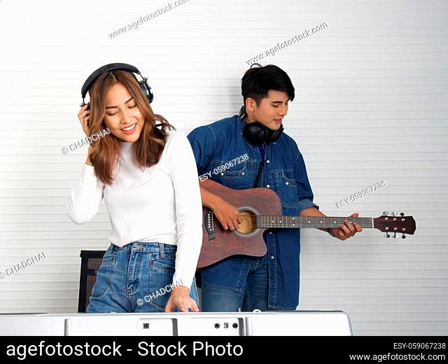 Young asian woman sing while playing an electric keyboard in front of white walls. Her boyfriend play the guitar together