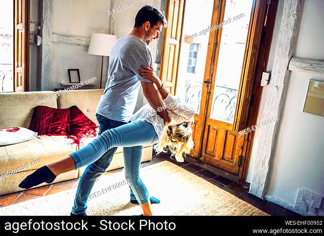 Young couple dancing in living room at home
