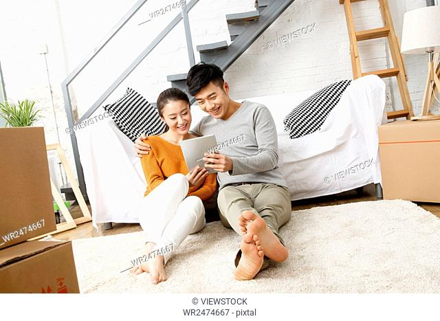 The young couple sat on the carpet using a tablet