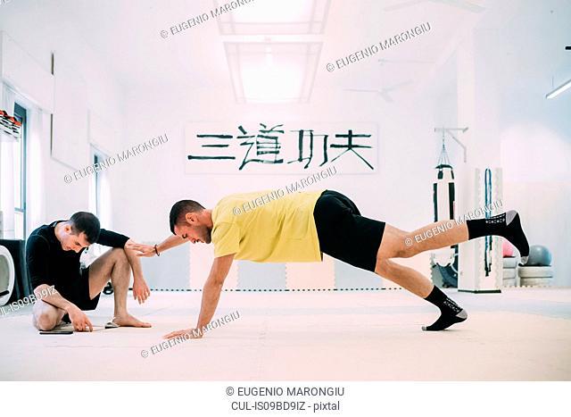Man with coach doing push ups