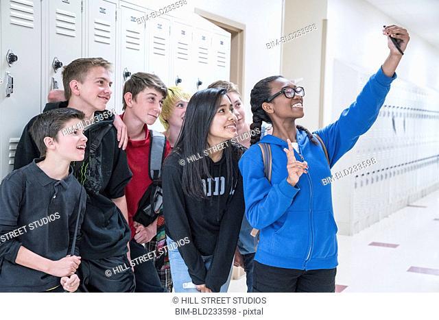Friends posing for cell phone selfie in school corridor