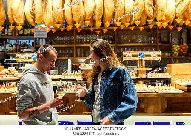 "Young couple eating ""Pintxos"" at the Meson Portaletas, Parte Vieja, Old town, Donostia, San Sebastian, Gipuzkoa, Basque Country, Spain"