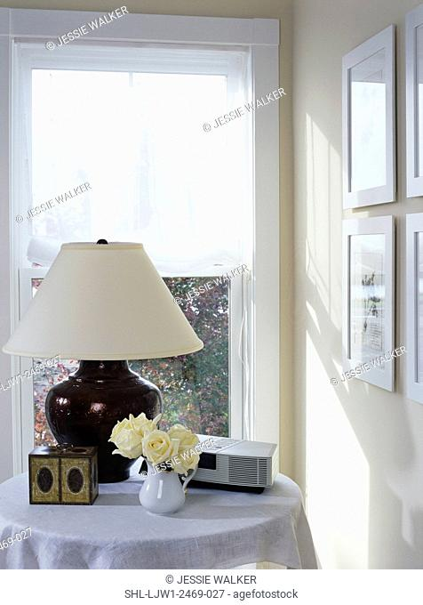 BEDROOMS: Corner round bedside table, window shade, lamp, floral arrangement of white roses, simple clean lined, light yellow and white