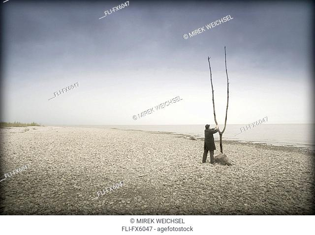 Man in Hat and Coat Standing on Beach Adjusting Large Branch, Winnipeg, Manitoba