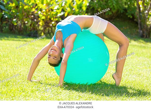 happy young woman trains with exercise ball outdoor in park