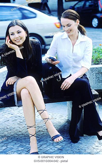 Young women sitting together on a bench