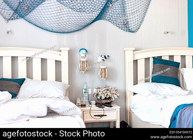 Used linens. Bedsheet and pillows. Messed up bedsheet and linens. Fishing net hanging by the wall