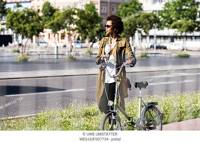 Young woman with smartphone and earphones pushing bicycle