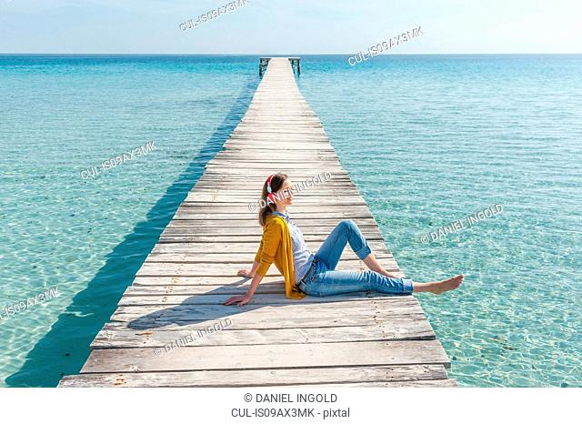 Mid adult woman relaxing on pier, wearing headphones