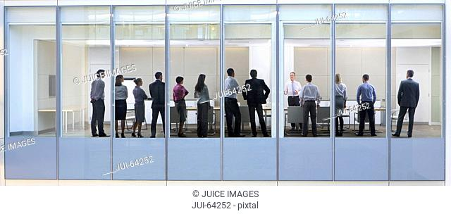 View through window, of people standing in business meeting