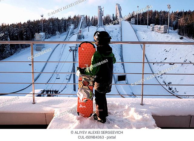 Rear view of boy with snowboard at top of ski slope