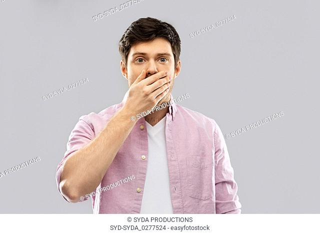 shocked young man covering his mouth by hand