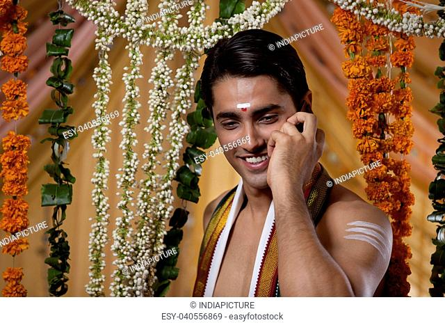 Close-up of young smiling groom having conversation on cell phone