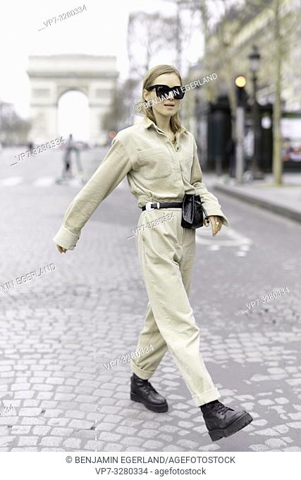fashionable woman walking at street during fashion week, Arc de Triomphe in background, in Paris, France