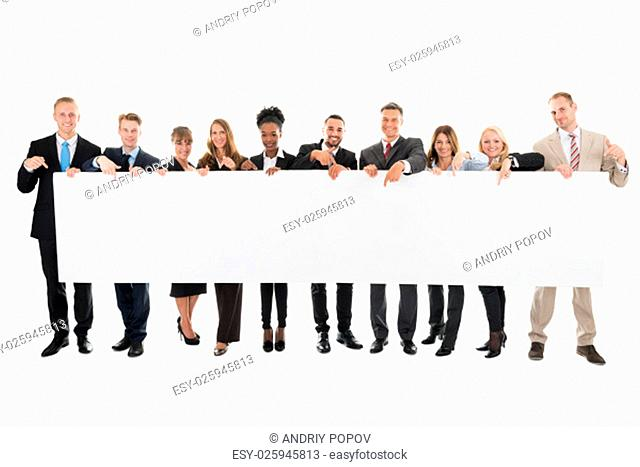 Full length portrait of happy business team pointing at blank billboard against white background