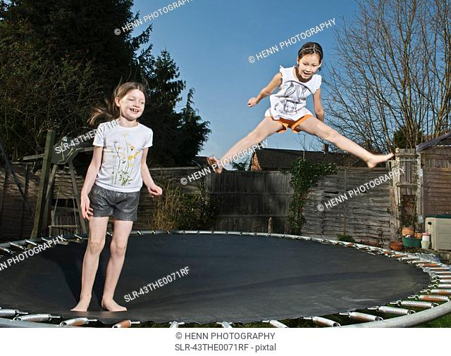 Girls jumping together on trampoline