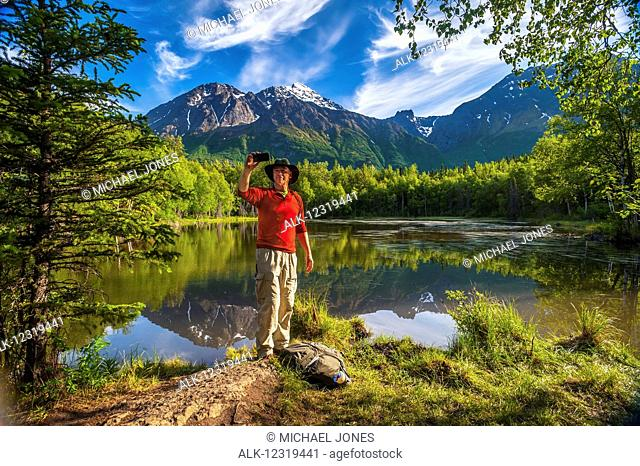 Hiker taking a selfie next to Dew Pond in the Chugach State Park near Eagle River, Southcentral Alaska, summer