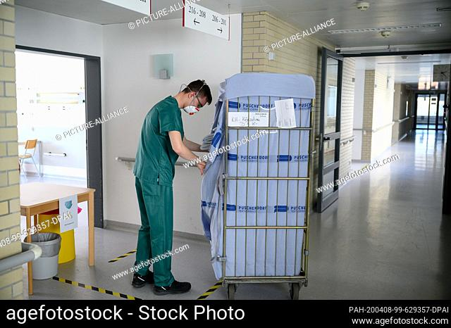 06 April 2020, Baden-Wuerttemberg, Künzelsau: An employee in an isolation ward in a former clinic takes towels from a car