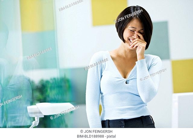 Japanese businesswoman laughing in office